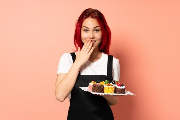 분홍색 벽에 고립 된 머핀을 들고 생과자 요리사 행복 하 고 손으로 취재 입 취재