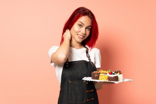 분홍색 벽 웃음에 고립 된 머핀을 들고 생과자 요리사