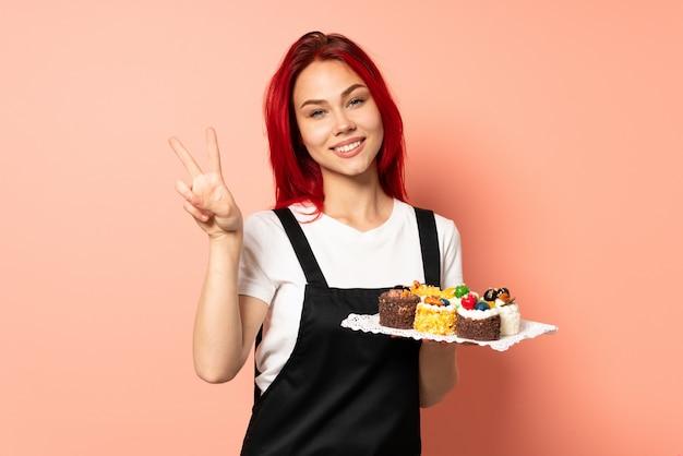 양손으로 승리 기호를 보여주는 분홍색 벽에 고립 된 머핀을 들고 생과자 요리사