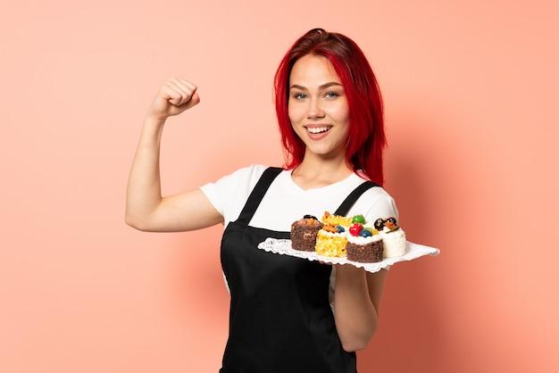 승리를 축하 핑크 벽에 머핀을 들고 생과자 요리사