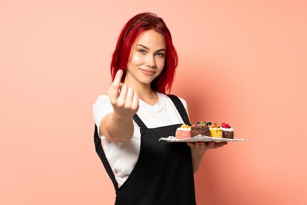 오는 제스처를 하 고 분홍색 벽에 머핀을 들고 생 과자 요리사