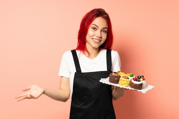 행복하고 웃는 분홍색 벽에 머핀을 들고 생과자 요리사