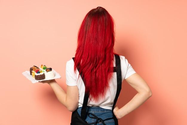 다시 위치에 분홍색 벽에 머핀을 들고 생과자 요리사