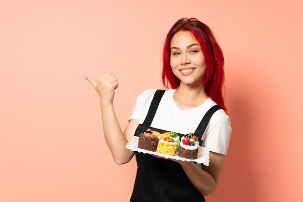측면을 가리키는 분홍색 벽에 머핀을 들고 생과자 요리사