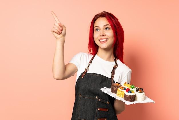 검지 손가락으로 가리키는 좋은 아이디어 핑크 벽에 머핀을 들고 생과자 요리사