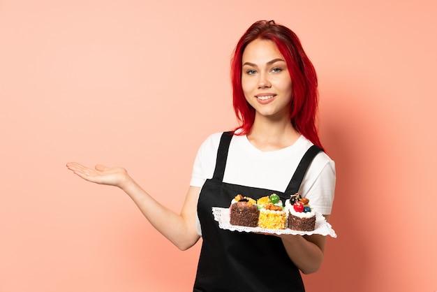 쪽으로 향하고 웃고있는 동안 아이디어를 제시하는 핑크 벽에 머핀을 들고 생과자 요리사