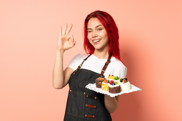 손가락으로 확인 표시를 보여주는 분홍색 벽에 머핀을 들고 생과자 요리사