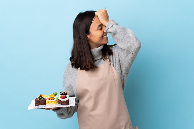 Pastry chef holding a big cake over blue wall has realized something and intending the solution.