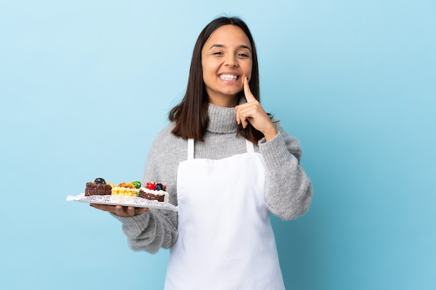 Pastry chef holding a big cake over isolated blue background smiling with a happy and pleasant expression.
