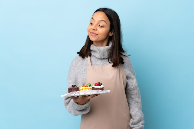 Pastry chef holding a big cake over isolated blue having doubts while looking side