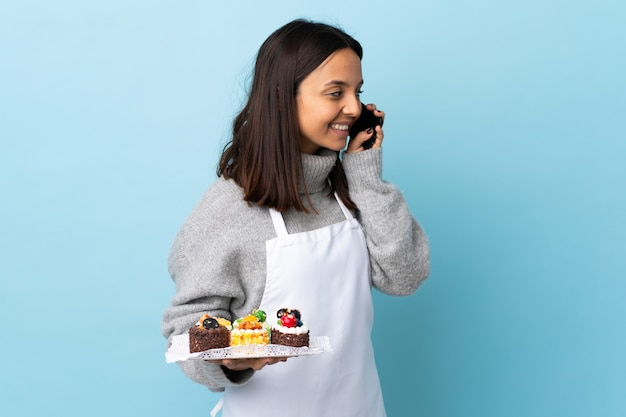 Pastry chef holding a big cake over isolated blue keeping a conversation with the mobile phone with someone