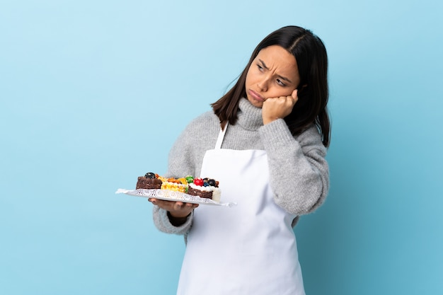Pastry chef holding a big cake over isolated blue wall with tired and bored expression