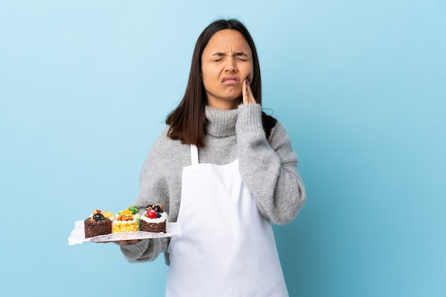 Pastry chef holding a big cake over isolated blue wall with toothache