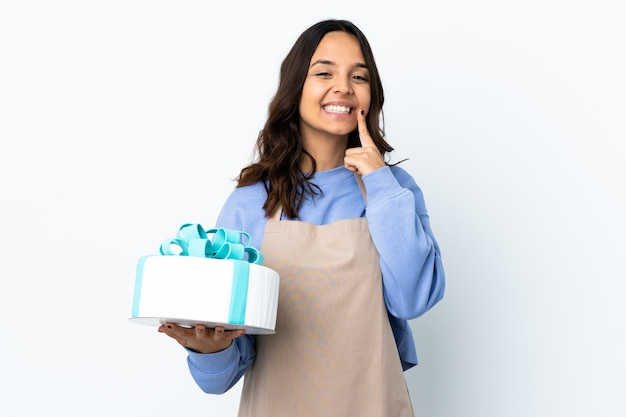 Pastry chef holding a big cake over isolated white background smiling with a happy and pleasant expression