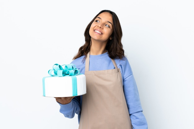 Pastry chef holding a big cake over isolated white background thinking an idea while looking up