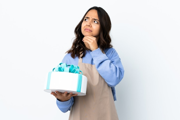 Pastry chef holding a big cake over isolated white wall having doubts and with confuse face expression