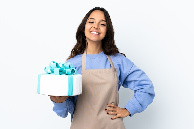 Pastry chef holding a big cake over isolated white wall posing with arms at hip and smiling