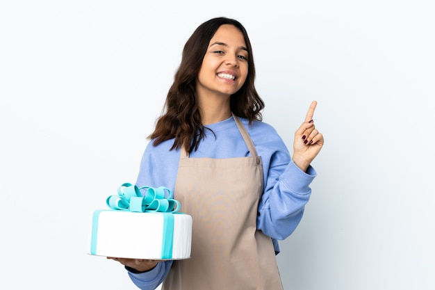 Pastry chef holding a big cake over isolated white wall showing and lifting a finger in sign of the best