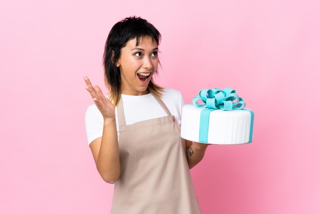 Pastry chef holding a big cake over pink wall with surprised facial expression