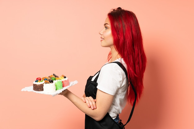 Pastry chef holding a muffins isolated on pink wall in lateral position