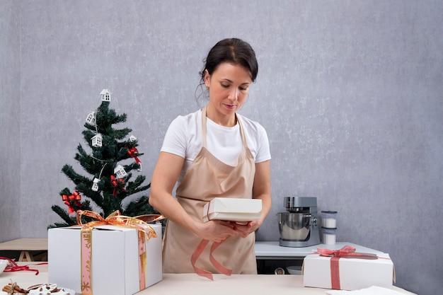 パティシエは甘い贈り物をギフトボックスに詰めます。 Premium写真