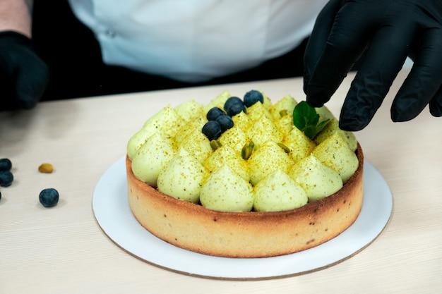 생과자 요리사는 휘핑 크림과 함께 피스타치오 쇼트 브레드 타르트에 블루 베리를 넣습니다.