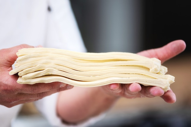 Pastry chef showing dough sheets ready to be rolled to produce croissant.