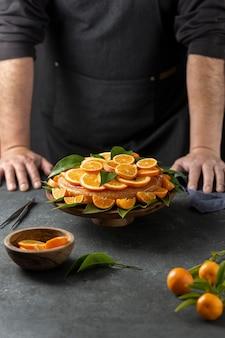 オレンジ色のケーキの後ろに立っているパティシエ