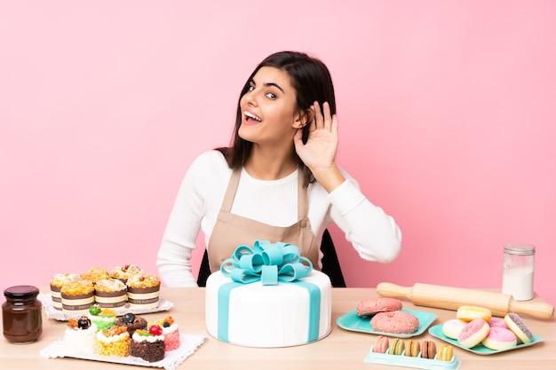 耳に手を置いて何かを聞いている孤立したピンクの上にテーブルに大きなケーキを持つパティシエ