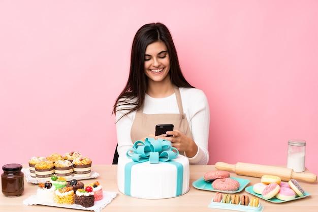 Шеф-кондитер с большим тортом на столе над изолированной розовой стеной отправляет сообщение с мобильного телефона