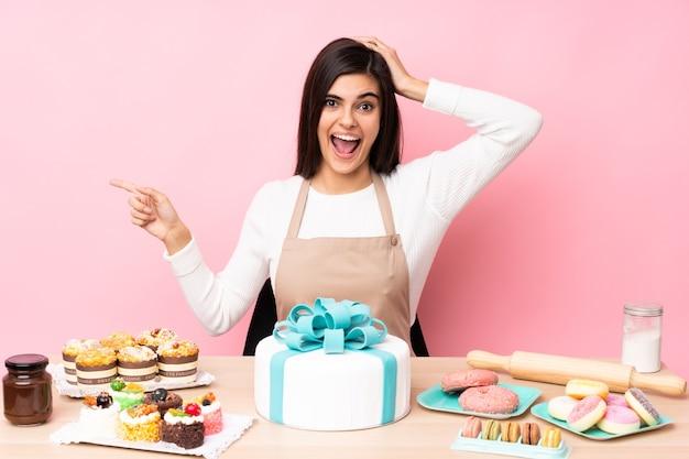 孤立したピンクの壁の上のテーブルに大きなケーキを持ったパティシエが驚いて、人差し指を横に向ける