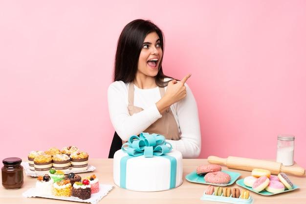 孤立したピンクの壁の上のテーブルに大きなケーキを持つパティシエは驚いて、側を指しています