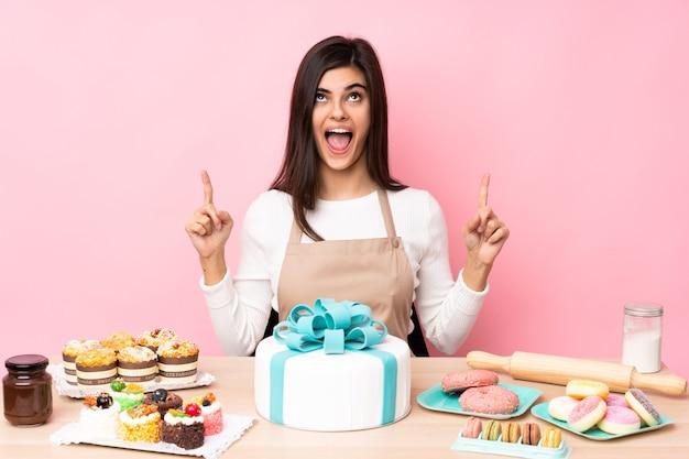 孤立したピンクの壁の上のテーブルに大きなケーキを持つパティシエは驚いて上向き