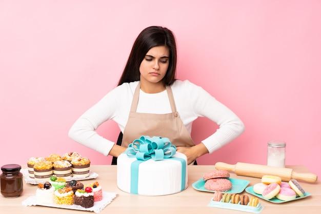 孤立したピンクの上にテーブルに大きなケーキを持つパティシエ