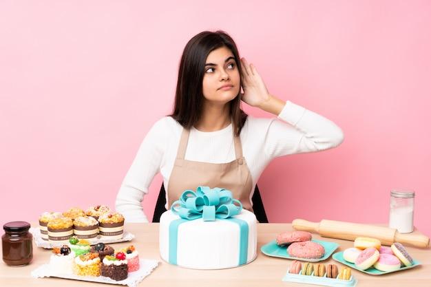 耳に手を当てて何かを聞いているピンクの壁の上のテーブルに大きなケーキを持つパティシエ