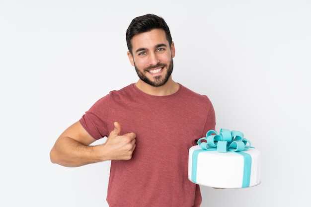 Pastry chef with a big cake isolated on white wall with thumbs up because something good has happened