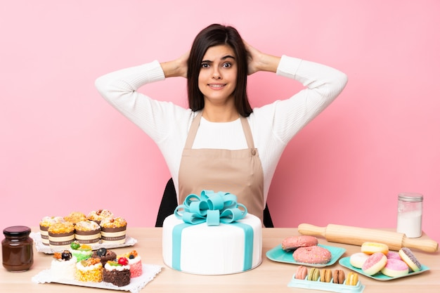 Pastry chef with a big cake in a table over isolated pink wall frustrated and takes hands on head