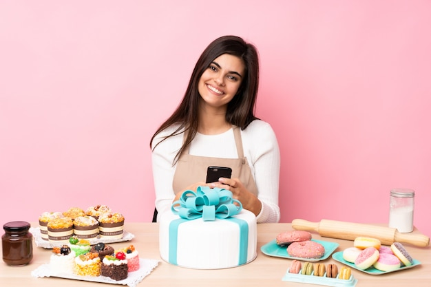 Pastry chef with a big cake in a table over isolated pink wall sending a message with the mobile