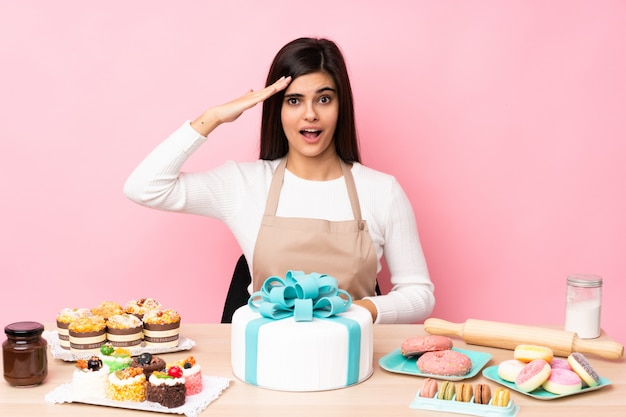 Pastry chef with a big cake in a table over pink wall has just realized something and has intending the solution