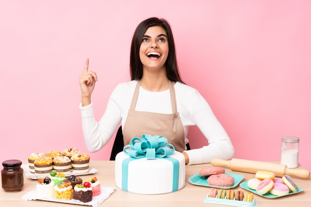 Pastry chef with a big cake in a table over pink wall pointing up and surprised