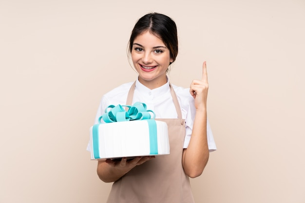 Pastry chef woman holding a big cake pointing up a great idea