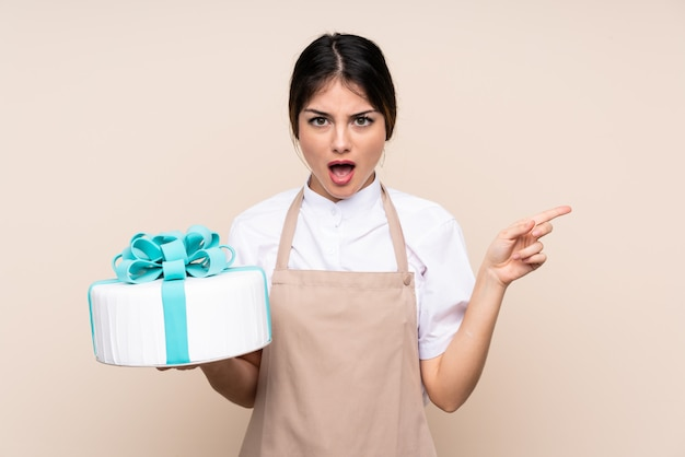 Pastry chef woman holding a big cake over wall surprised and pointing side