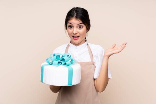 Pastry chef woman holding a big cake over wall with shocked facial expression