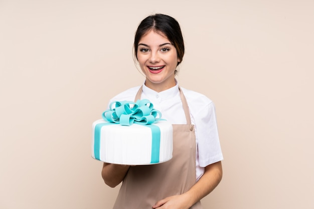Pastry chef woman holding a big cake over wall with surprise and shocked facial expression