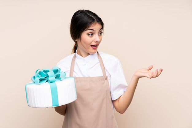 Pastry chef woman holding a big cake over wall with surprised facial expression