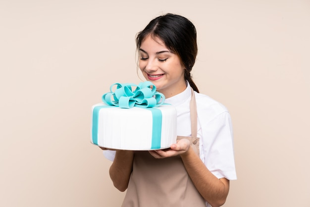 Pastry chef woman holding a big cake