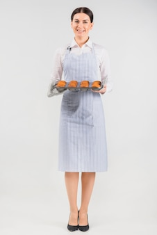 Pastry chef woman holding muffins