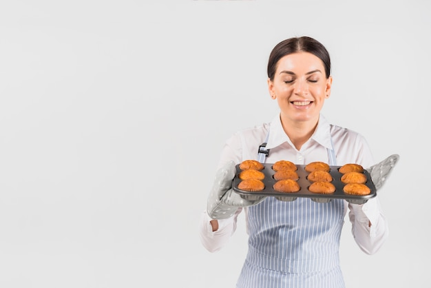Pastry cook female smelling muffins