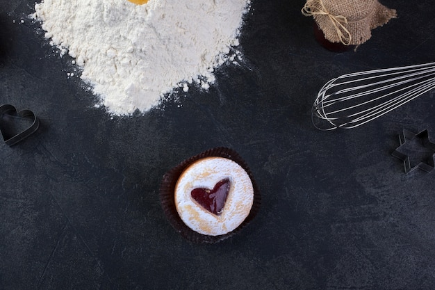 Pastry cookie with a red jam heart and icing powder sugar
