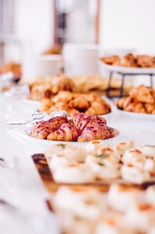 Pastry cookies and croissants sweet desserts served at charity event  food drinks and menu concept a...